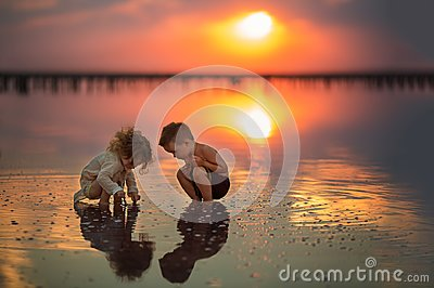Two small children playing on the seashore during sunset