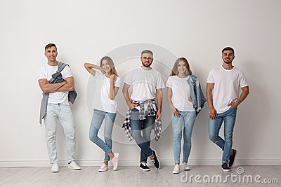 Group of young people in jeans near wall