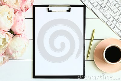 Office desk table with cup of coffee, pink peony flowers, golden pen, blank paper and clipboard.