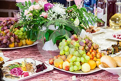 Served table at the Banquet. Fruits, snacks, delicacies and flowers in the restaurant. Solemn event or wedding