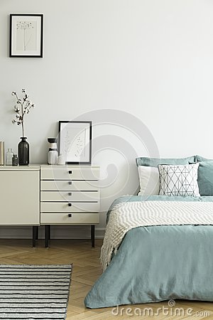Posters and cabinet with plant in white bedroom interior with bl