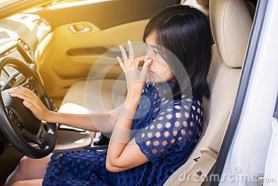 Woman hand squeeze her nose with of bad smell in a car