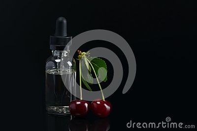 Aroma oils in a can with a dispenser, next to the fruit of ripe cherries. lying on black background
