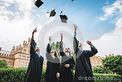 Graduates near university are throwing up hats in the air.