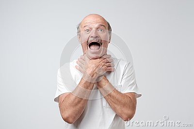 Mature european man in white tshirt shouting and suffocate because painful strangle. Health problem.