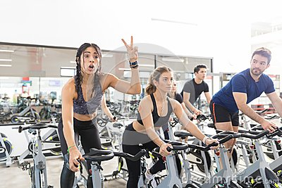 Woman Gesturing Victory While Exercising On Spinning Bike In Gym