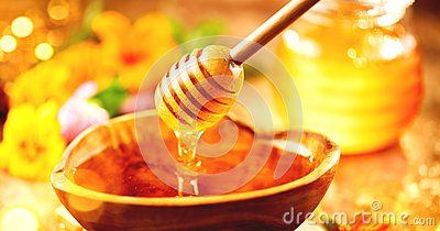 Honey. Healthy organic thick honey dripping from the honey dipper in wooden bowl. Sweet dessert