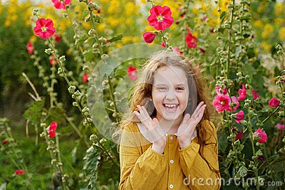 Little girl having happy eyes raising her hands up and shows white teeth.