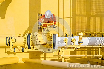 stock image of offshore oil and gas site service operator open valve for control gases and crude product, petroleum and chemical industry busines