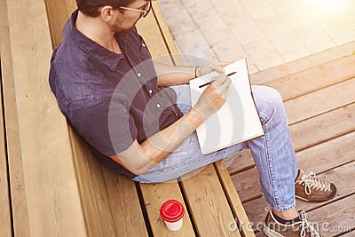 Man reading book sitting outside in public space. Wearing glasses alone working. Concept of education or busyness