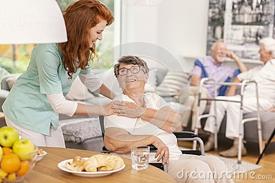 Friendly nurse supporting smiling senior woman in nursing house.