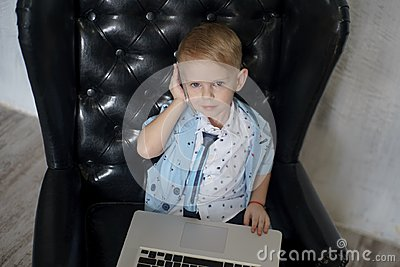 Young businessman using a laptop. funny child in glasses. Fashion portrait of little handsome boy in office