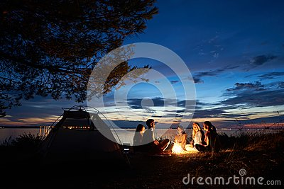 Night summer camping on shore. Group of young tourists around campfire near tent under evening sky