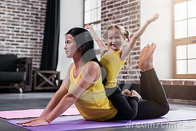 Young Caucasian mother doing yoga cobra pose on floor while her smiling daughter sitting on moms back