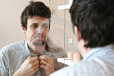 Tired sleepy man who has just woken up looks at his reflection in the mirror and sees his scruffy appearance, buttoning