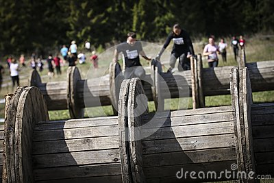 Muddy obstacle race runner in action. Mud run