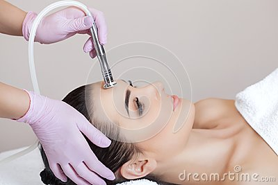 The cosmetologist makes the procedure Microdermabrasion of the facial skin of a beautiful, young woman in a beauty salon
