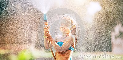 stock image of cute little girl sprinkls a water for herself from the hose, makes a rain. pleasure for hot summer days