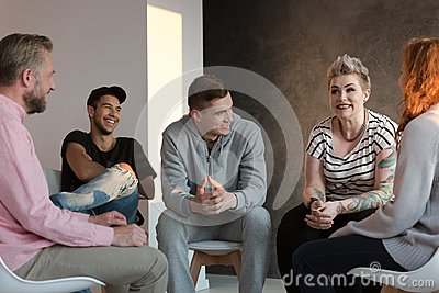 Teenagers laughing during a group counseling session for youth