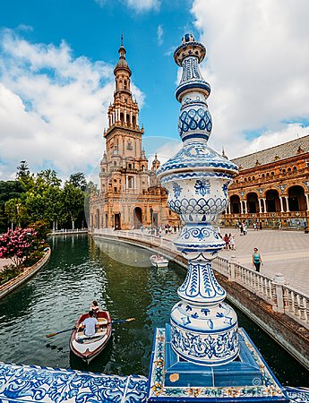 Juxtaposition of blue and white ceramic azulejo tiles against one of the baroque sandstone tower at Plaza de Espana in Seville, Sp