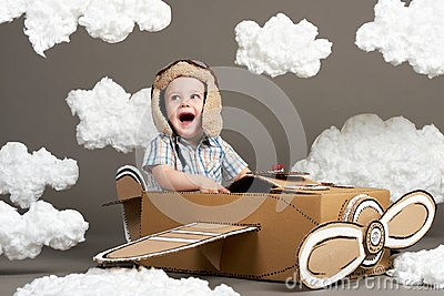 The boy plays in an airplane made of cardboard box and dreams of becoming a pilot, clouds from cotton wool on a gray background, r