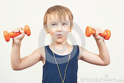Healthy little boy working out with dumbbells over white background. Healthy lifestyle, kids sports and childhood. Cute kid boy ex