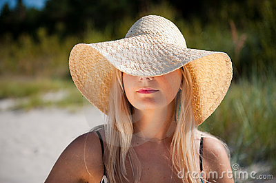Young pretty woman with hat relaxing on the beach