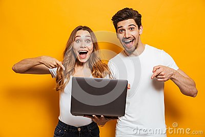 Portrait of pleased positive man and woman holding and pointing