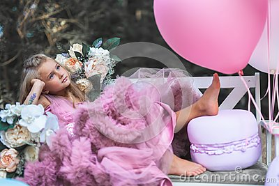 Cute little girl holds French Macaron. Confectionery concept