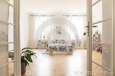 Sun shinning through windows into a spacious stylish bedroom interior in a villa. Big bed with bedding standing on herringbone par