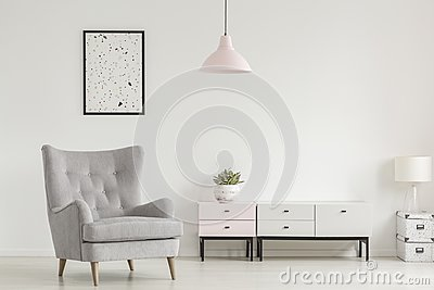 Poster above grey armchair and lamp in white living room interior with plant on cabinet. Real photo