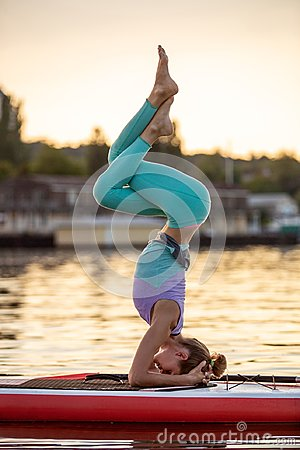 Sporty woman in yoga position on paddleboard, doing yoga on sup board, exercise for flexibility and stretching of