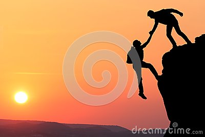 Teamwork couple hiking help each other trust assistance silhouette in mountains, sunset. Teamwork of two men hiker helping each ot