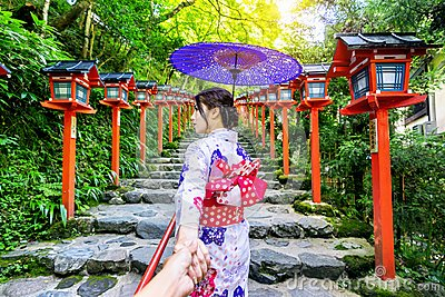 Woman wearing japanese traditional kimono holding man`s hand and leading him to Kifune shrine, Kyoto in Japan