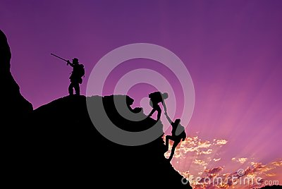 Hikers climbing on rock, mountain at sunset, one of them giving hand and helping to climb.Teamwork , Helps ,Success, winner and Le
