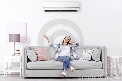 Young woman operating air conditioner while sitting