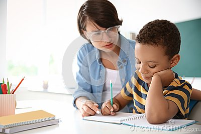 Female teacher helping child with assignment