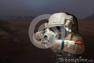 Spaceman with a camera in a space suit on the planet Mars.