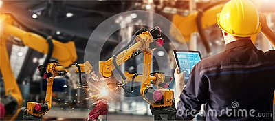 Engineer check and control welding robotics automatic arms machine in intelligent factory automotive industrial with monitoring sy