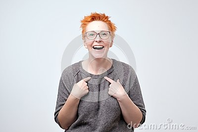 Happy mature woman with red hair pointing fingers at herself. Select me please concept