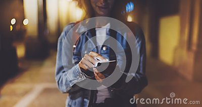 Woman pointing finger on blank screen smartphone on background bokeh light in night atmospheric city, blogger hipster using in han