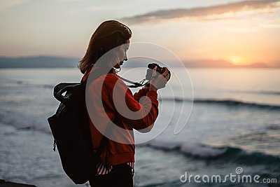 Hipster hiker tourist with backpack making photo of seascape sunset on camera on background sea, photographer enjoying ocean horiz