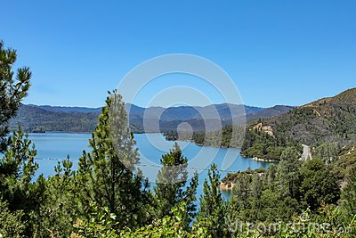 Overlooking Wiskey Lake in Northern California surrounded by pine trees with a twisting road headed west through the mountians