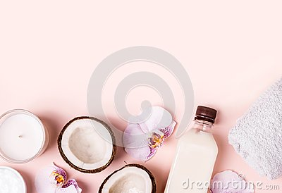 Coconut oil and halves of fresh coconut on a pink background. Hair care spa concept