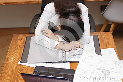 Tired overworked young Asian business woman bend down head on workplace in office.