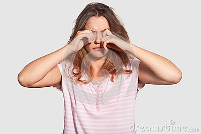Hard awakening concept. Sleepy young attractive woman rubs eyes, has mess on head, awakes very early, dressed in casual clothes, c