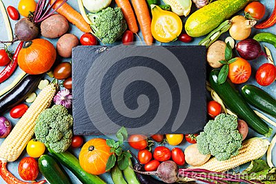 Autumn farm vegetables, root crops and slate cutting board top view with copy space for menu or recipe. Healthy food background.