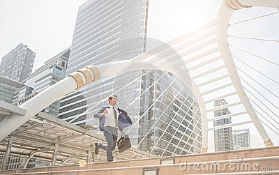 Running business man in front of buildings hurry and rush because work late.