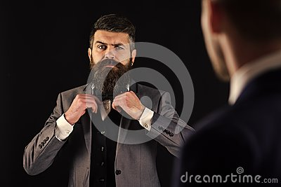 Meeting of reputable businessmen, black background. Man with beard on serious face, ties bow tie before meeting