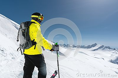 Portrait of a professional freerider skier standing on a snowy slope against the background of snow-capped mountains